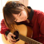 ギターを弾く女性の写真